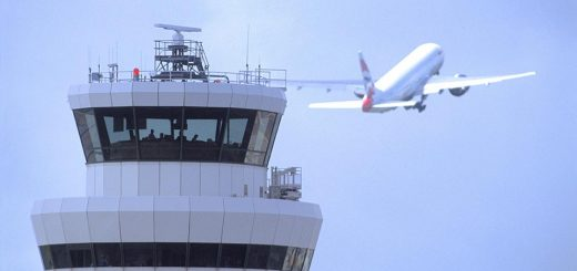 Airport control tower with large passenger plane taking off in the distance